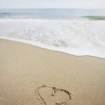Hearts drawn on sandy beach