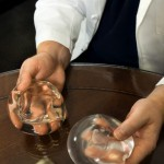 Doctor Holding Breast Implants